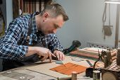 Man working with leather textile at a workshop. Craftman cutting leather. Concept of handmade craft  poster