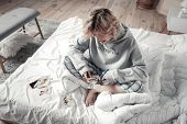 Top View Of Ex Wife Wearing Pajamas Sitting In Bed And Cutting Photo poster