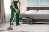 Professional Janitor Removing Dirt From Carpet With Vacuum Cleaner In Bedroom, Closeup. Space For Te poster