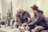 Young-adult Short-haired Son Comforting Elderly Grey-haired Upset Father At Living-room. poster