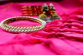 Indian Bracelets With White Pearls Lie On A Pink Ethnic Fabric With Tufts On The Background Of Red B poster
