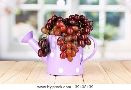 Ripe grapes in watering can on wooden table on window background