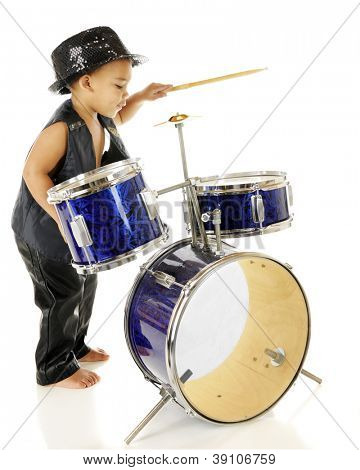 Profile of an adorable preschooler playing the drums in his sparkly fedora and black leather vest and pants.  Barefoot.  On a white background.
