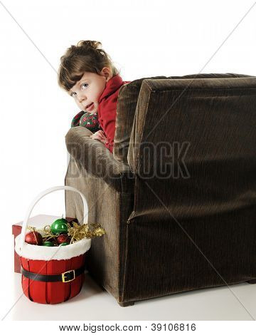 An adorable preschooler in her pajamas.  She's looking back at the viewer for her overstuffed chair with a basket of Christmas decorations nearby.  On a white background.