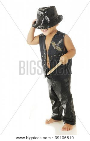 A happy, barefoot preschooler in black leather vest and pants with a sparkly fedora covering his eyes.  On a white background.