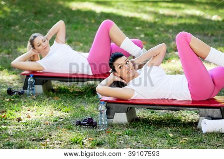 Young women exercising doing sit-ups in the park
