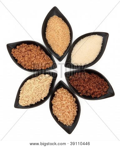 Selection of demerara, granulated, molasses, muscovado, crystal and light brown sugar in black leaf shaped dishes over white background.