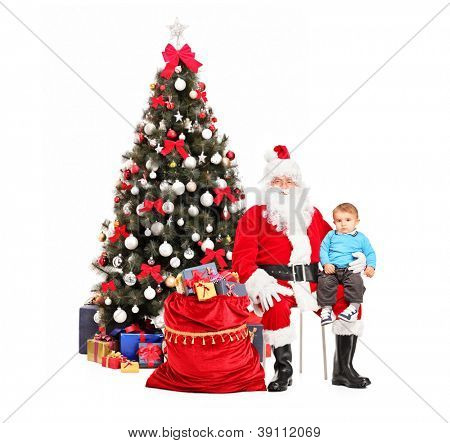 Santa Claus and child on his lap posing, a christmas tree in the background