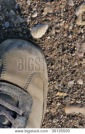 Hiking Boot Off-road Shoe On Hard Arid Dried Soil, Vertical Close Up, Detailed Macro Of Bare Earth