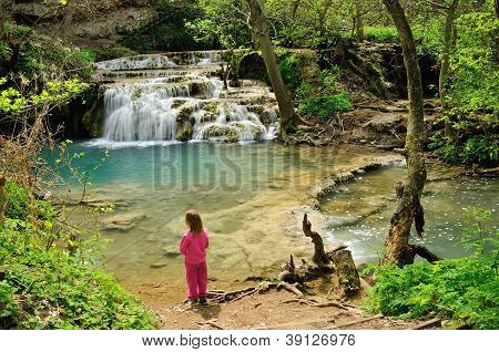 The boy looking the beautiful river and waterfall in the forest