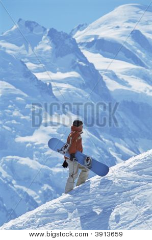 Man Walking Up Mountain With Snowboard