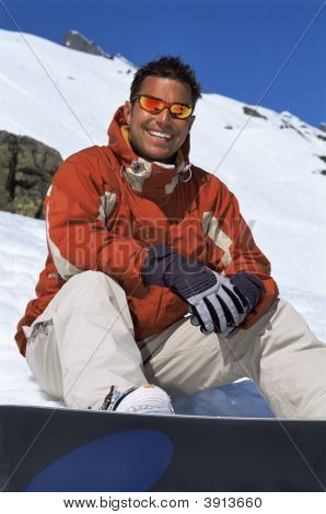 Man Resting In Snow With Snowboard