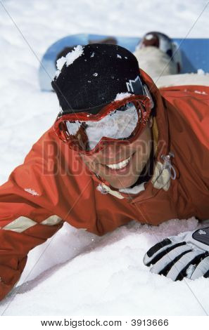 Man Laying In Snow With Snowboard