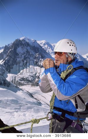 Man Mountain Climbing In Snow Warming Hands Up