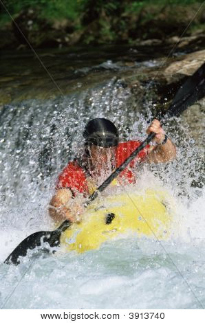 Man Canoeing Along Fast Flowing Water