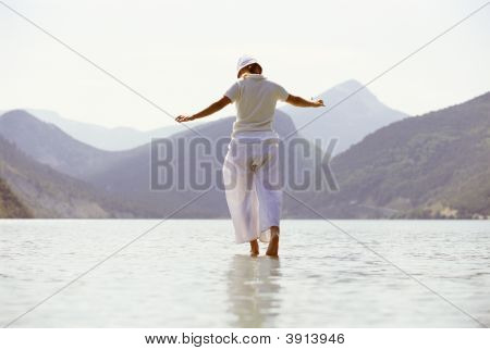 Woman Tiptoeing Through Water By Mountains