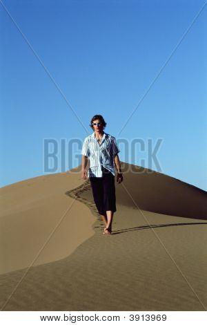 Homem caminhando em direção a câmera no deserto