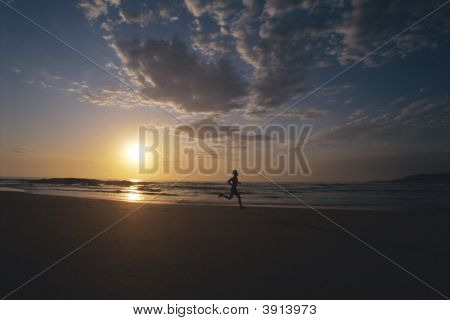 Man Running Along Beach With Sun Going Down