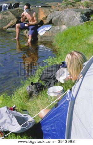 Couple Camping By River With Man Shaving