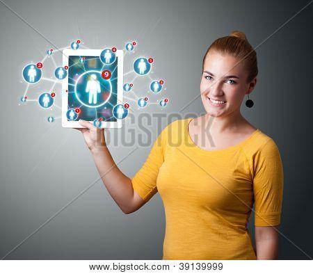Schöne junge Frau Betrieb Tablet mit sozialen Netz-Ikonen