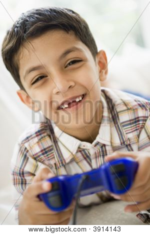 Middle Eastern Child Playing On Games Console At Home