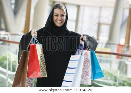 Middle Eastern Woman Stood In Shopping Mall With Bags