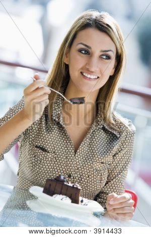 Middle Eastern Woman Eating Chocolate Cake In Shopping Mall