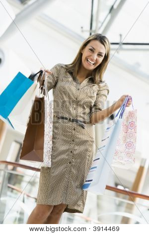 Middle Eastern Woman Standing In Shopping Mall With Bags