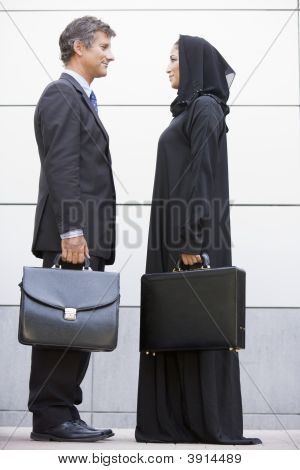 Middle Eastern Woman And Western Man Standing With Brief Cases