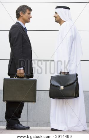 Middle Eastern And Western Business Men Facing One Another