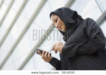 Middle Eastern Business Woman Stood Outside Offices With Cell Phone