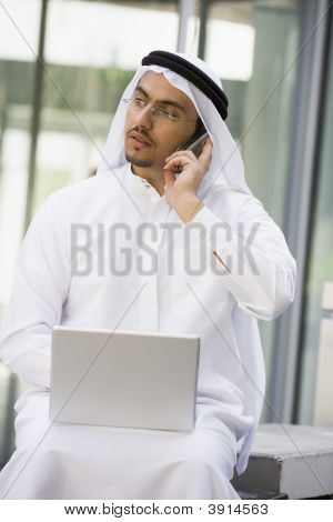Middle Eastern Business With Man On Laptop And Cell Phone