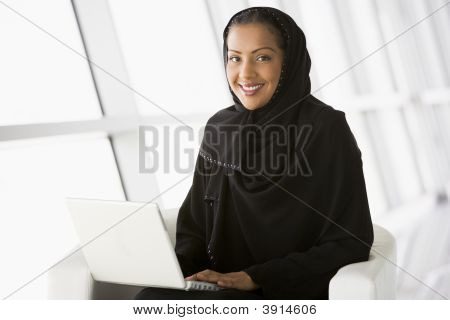 Middle Eastern Business Woman Sat On Chair With Laptop
