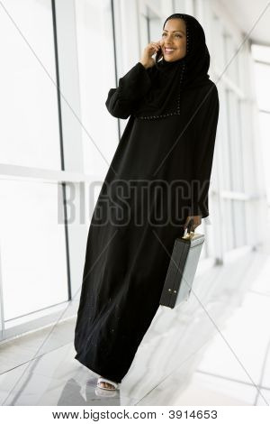 Middle Eastern Business Woman Walking Down Corridor On Cell Phone