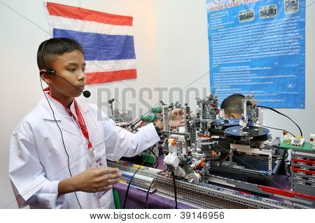 SUBANG JAYA - NOVEMBER 10: An unidentified student from Thailand explains his project at the World Robot Olympaid on November 10, 2012 in Subang Jaya, Malaysia. The theme is Robots connecting people.