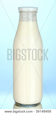 bottle of milk on blue background close-up