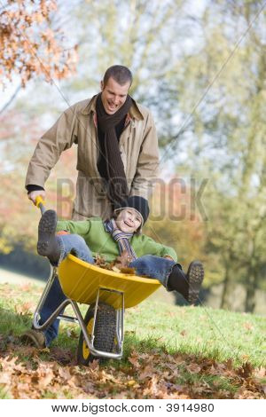Man Pushing Child In Wheelbarrow