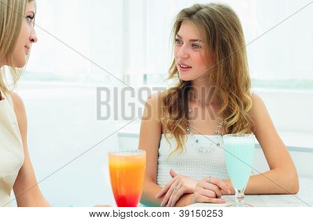 two beautiful women chatting in a cafe
