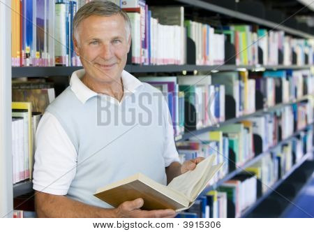 Senior Man In Library With Book