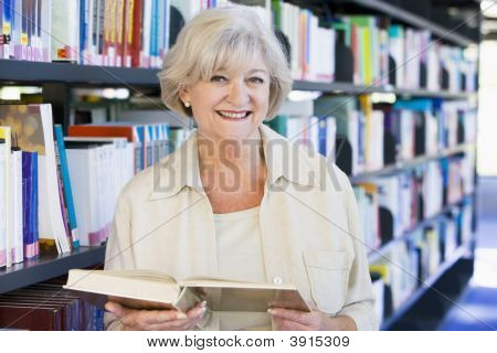 Senior Woman In Library With Book