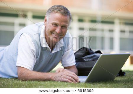 Senior Woman Using Laptop Outside School