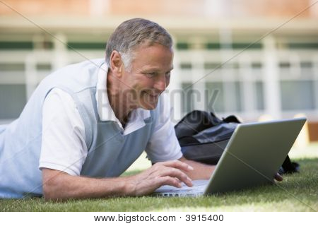 Senior Man Using Laptop Outside School