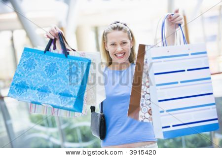 Woman In Shopping Mall Holding Up Bags