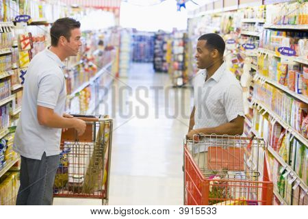 Men Chatting In Supermarket With Trolleys