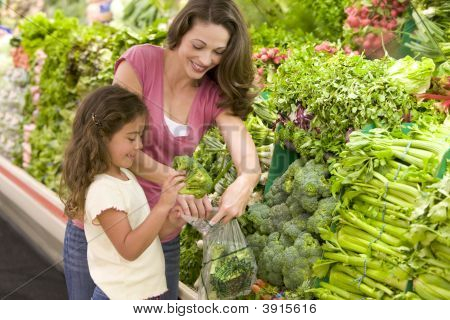 Woman And Child Choosing Vegetables From Shop