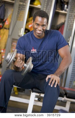 Firefighters Sat On Bench By Lockers Lifting Weights