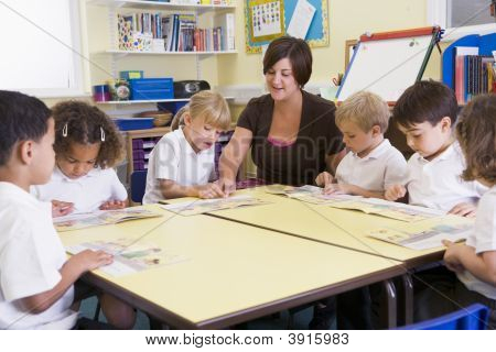 Teacher Helping Children To Read