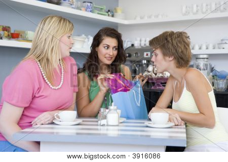 Girlfriends Showing Purchases Around Table