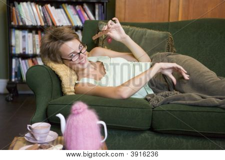 Woman Eating Chocolate On Sofa