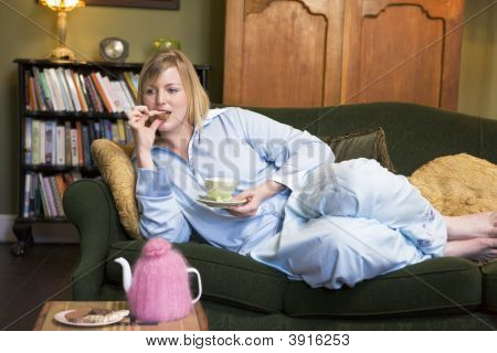 Woman Laid On Sofa Drinking Tea And Eating